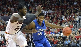 Duke's Amile Jefferson, right, attempts to drive past the defense of Louisville's Montrezl Harrell during the second half of an NCAA college basketball game, Saturday, Jan. 17, 2015, in Louisville, Ky. Duke won 63-52. (AP Photo/Timothy D. Easley)