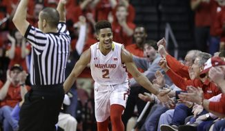 Maryland guard Melo Trimble (2) high-fives fans after scoring a 3-point basket in the first half of an NCAA college basketball game against Michigan State, Saturday, Jan. 17, 2015, in College Park, Md. Trimble contributed 24 points to Maryland's 75-59 win. (AP Photo/Patrick Semansky)