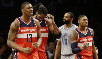 Washington Wizards' Kevin Seraphin (13) and Bradley Beal (3) celebrate a score by Nene Hilario, blocked from view, during the second half of an NBA basketball game against the Brooklyn Nets Saturday, Jan. 17, 2015, in New York. The Wizards won the game 99-90. (AP Photo/Frank Franklin II)