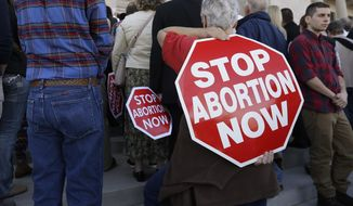 A woman carries an anti-abortion sign on her back during a rally at the Arkansas state Capitol in Little Rock, Ark., Sunday, Jan. 18, 2015. Women in Arkansas seeking abortion-inducing medication would have to take it in the presence of a doctor and come back for a follow-up days later under a bill filed Thursday in the Arkansas Legislature. (AP Photo/Danny Johnston)