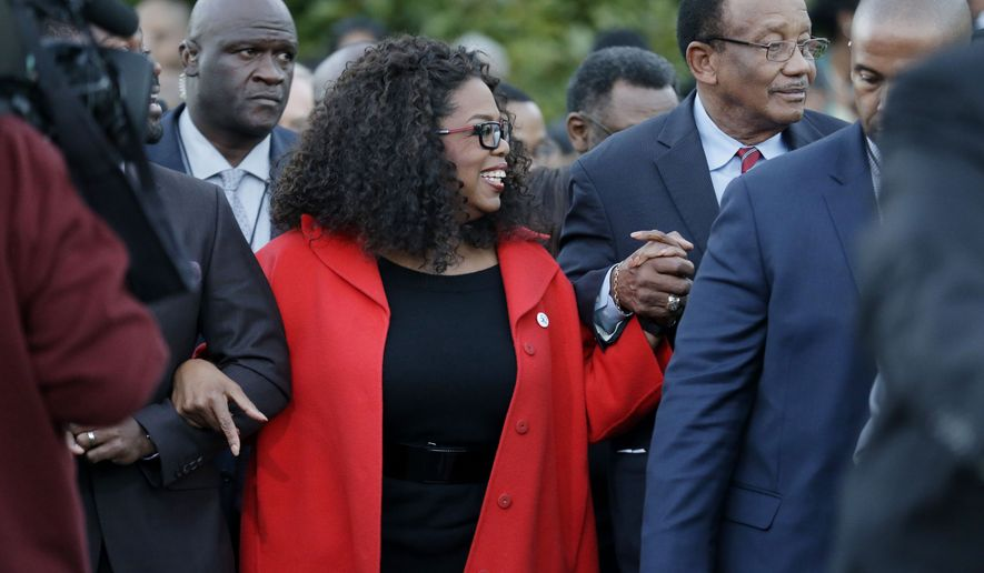 """Oprah Winfrey locks arms with some of the cast of the new movie """"Selma"""" as they march to the Edmund Pettus Bridge in honor of Martin Luther King Jr., Sunday, Jan. 18, 2015, in Selma, Ala. (AP Photo/Brynn Anderson)"""