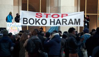 Men hold a banner during a gathering at the Trocadero place, in Paris, Sunday, Jan. 18, 2015 to protest against extremist Islamic group Boko Haram after a large-scale attack in Baga, where as many as 2,000 people were massacred in a raid on January 7, 2015. Cameroon, Chad and Niger have launched a regional bid to combat the Boko Haram. (AP Photo/Thibault Camus)