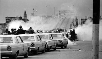 "In this March 7, 1965 file photo, tear gas fumes fill the air as state troopers, ordered by Alabama Gov. George Wallace, break up a demonstration march in Selma, on what is known as Bloody Sunday. A new march, led by Rev. Martin Luther King Jr., began March 21 and arrived in Montgomery on March 25, with the crowd swelling to 25,000 by the time they reached the Capitol. The 50th anniversary of the civil rights marches in Selma and the hit movie, ""Selma"" that tells the story are expected to bring thousands of visitors to this historic Alabama city. (AP Photo, File)"