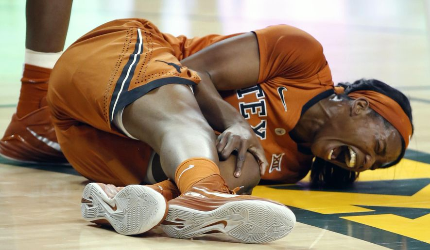 Texas forward Nneka Enemkpali (3) holds on to her leg after being injured while pulling down a rebound over Baylor in the first half of an NCAA college basketball game, Monday, Jan. 19, 2015, in Waco, Texas. (AP Photo/Rod Aydelotte)