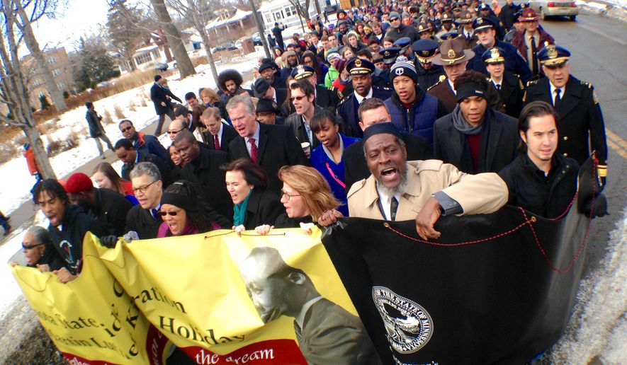 People march during a re-enactment to honor Rev. Martin Luther King Jr., Monday, Jan. 19, 2015, at Macalester College in St. Paul, Minn. (AP Photo/The St. Paul Pioneer Press, Ben Garvin) MINNEAPOLIS STAR TRIBUNE OUT