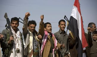 Houthi Shiite Yemenis raise their fists during clashes near the presidential palace in Sanaa, Yemen, Monday, Jan. 19, 2015. Rebel Shiite Houthis battled soldiers near Yemen's presidential palace and elsewhere across the capital Monday, despite a claim of a cease-fire being reached to halt the violence, witnesses and officials said. (AP Photo/Hani Mohammed)