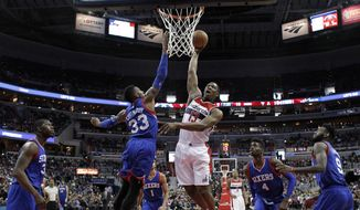 Washington Wizards center Kevin Seraphin (13), from France, dunks in front of Philadelphia 76ers forward Robert Covington (33) in the first half of an NBA basketball game, Monday, Jan. 19, 2015, in Washington. The Wizards won 111-76. (AP Photo/Alex Brandon)