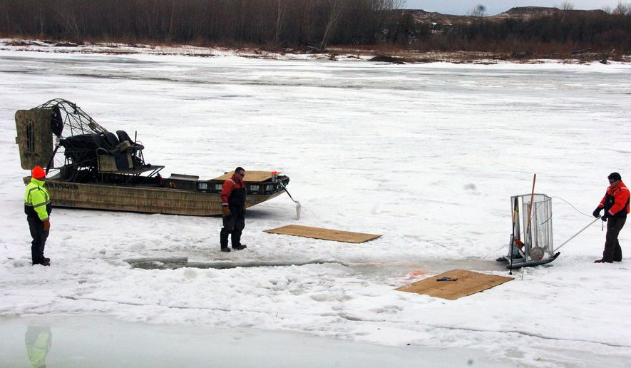 Cleanup workers cut holes into the ice on the Yellowstone River near Crane, Mont. on Monday, Jan. 19, 2015 as part of efforts to recover oil from an upstream pipeline spill that released up to 50,000 gallons of crude. (AP Photo/Matthew Brown)