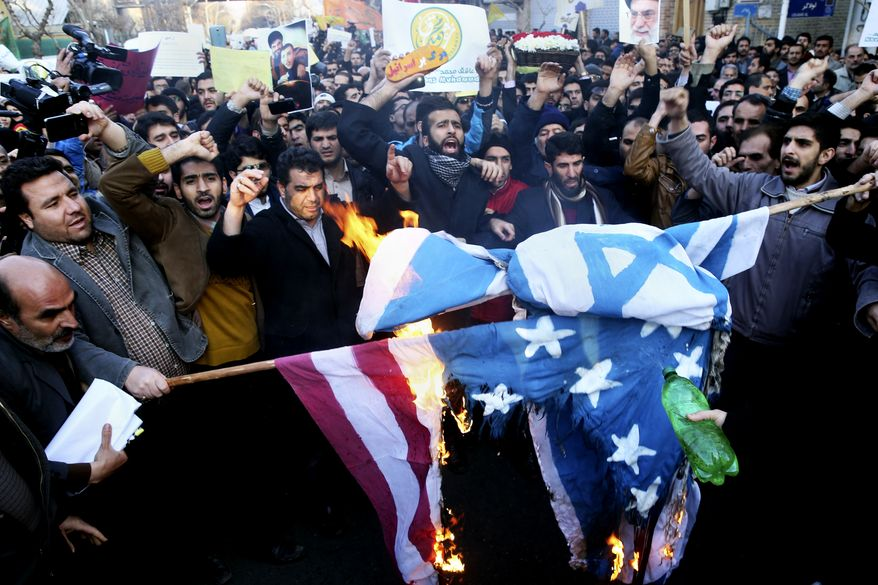 Iranian demonstrators burn representations of Israeli and U.S. flags during a rally against the satirical magazine Charlie Hebdo's latest publication of a cartoon depicting the Prophet Muhammad, which some Muslims deem an insult to Islam, in front of the French Embassy, Tehran, Iran, Monday, Jan. 19, 2015. (AP Photo/Ebrahim Noroozi)