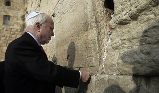 U.S. Senator John McCain places a note in the stones of the Western Wall, the holiest site where Jews can pray during his visit to Jerusalem's old city, Monday, Jan. 19, 2015. People of all faiths slip notes between the stones in the belief that god will answer their prayers. (AP Photo/Tsafrir Abayov)