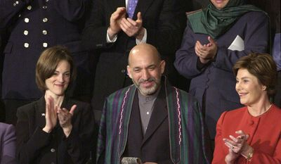 Afghan leader Hamid Karzai acknowledges applause on Capitol Hill Tuesday, Jan. 29, 2002 during President Bush's State of the Union address. Back row, from left are, Manassas, Va. firefighter William Best, Olympian skeleton competitor James Shea and Sadoozai Panah, managing director for Women's Development for Afghanistan, Front row, from left are, Shannon Spann, widow of CIA agent Michael Spann, Karzai and first lady Laura Bush.  (AP Photo/Susan Walsh)