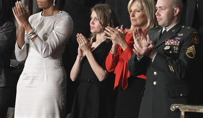 From left, first lady Michelle Obama, Brianna Mast, Jill Biden ad Staff Sgt. Brian Mast applaud during President Barack Obama's State of the Union address on Capitol Hill in Washington, Tuesday, Jan. 25, 2011.   (AP Photo/Charles Dharapak)