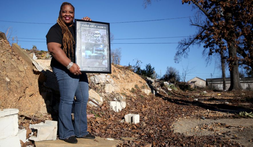 Blossom Rogers stands with a poster promoting her book on land in Alberta that will be the future location to a transitional home for recovering women, on Sunday, Jan. 18, 2015, in Tuscaloosa, Ala. Rogers, a former drug addict herself, has been clean for 10 years and hopes to be cutting the ribbon on the home in a year. (AP Photo, The Tuscaloosa News, Kirsten Fiscus)