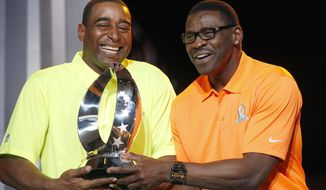 Michael Irvin, right, NFL Hall of Fame member and Pro Bowl Alumni captain, and Cris Carter, left, NFL Hall of Fame member and Pro Bowl Alumni captain, laugh as they playfully try to pull the Pro Bowl trophy away from one another during the Pro Bowl Kickoff news conference Tuesday, Jan. 20, 2015, in Phoenix.  The upcoming NFL Pro Bowl football game will be played on Sunday. (AP Photo/Ross D. Franklin)