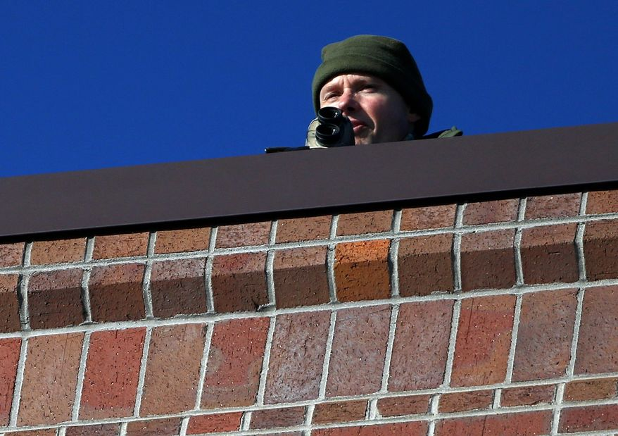 A security officer keeps watch from the roof of the Arapahoe County Justice Center, in Centennial, Colorado Tuesday, The jury selection process in the trial of Aurora theater shooting suspect James Holmes began Tuesday, and may take months. (Associated Press)