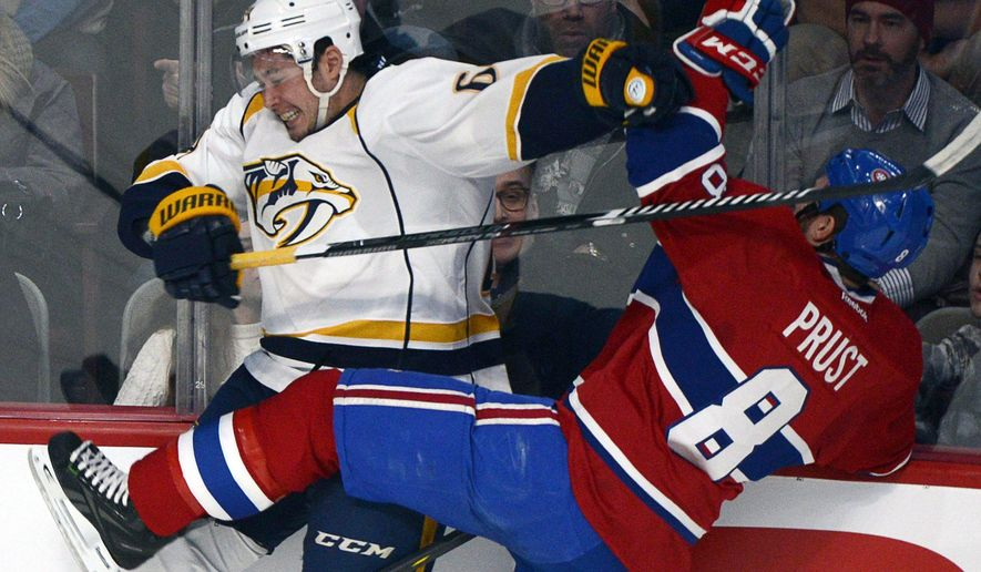Nashville Predators' Victor Bartley, left, is checked into the boards by Montreal Canadiens' Brandon Prust during the first period of an NHL hockey game Tuesday, Jan. 20, 2015, in Montreal. (AP Photo/The Canadian Press, Rayn Remiorz)