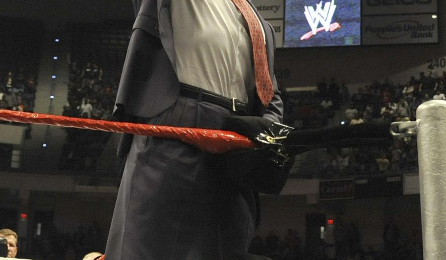 FILE - In this Oct. 30, 2010, file photo, World Wrestling Entertainment owner Vince McMahon raises his arm in the air to the audience during a fan appreciation event in Hartford, Conn. Two former professional wrestlers accuse the WWE of ignoring concussions they say left them with serious brain injuries. The plaintiffs, Evan Singleton, of Lancaster, Pa., and Vito LoGrasso, of Coatesville, Pa., have filed a potential class-action lawsuit in federal court in Philadelphia. That's where a judge is weighing a similar case that could yield a $1 billion settlement for thousands of former NFL players. (AP Photo/Jessica Hill, File)