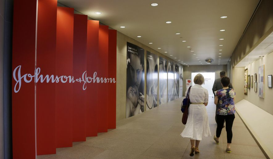 FILE - In this Tuesday, July 30, 2013, file photo, people walk along a corridor at the headquarters of Johnson & Johnson in New Brunswick, N.J. Johnson & Johnson on Tuesday, Jan. 20, 2015 said its fourth-quarter profit dropped 28 percent as lower sales overseas, mainly because of unfavorable currency exchange rates, dragged down revenue for its consumer and medical device businesses. (AP Photo/Mel Evans, File)