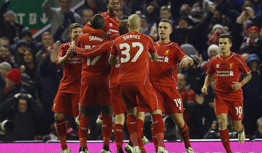 Liverpool's Raheem Sterling, top, celebrates his goal with teammates during the English League Cup semi-final first leg soccer match between Liverpool and Chelsea at Anfield Stadium, Liverpool, England, Tuesday Jan. 20, 2015. (AP Photo/Jon Super)