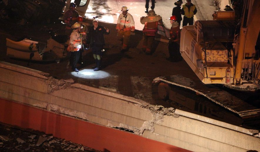 Police, fire and rescue workers respond to an overpass collapse on I-75 just north of the new Hopple Street bridge Tuesday, Jan. 20, 2015. A construction worker was killed and a tractor-trailer driver injured when an interstate overpass undergoing demolition collapsed in Cincinnati, fire and emergency medical officials said.(AP Photo/The Cincinnati Enquirer, Cameron Knight)