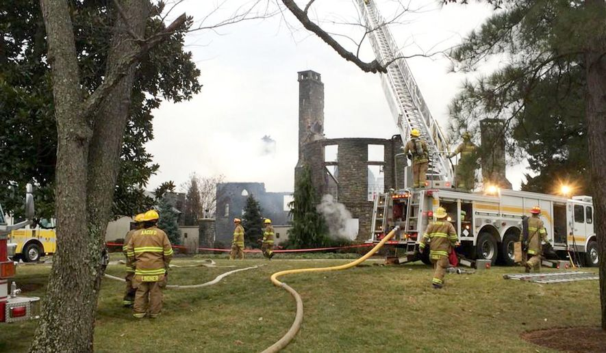 CORRECTS SOURCE - Firefights work to put out a fire at a home on Childs Point Road, Monday, Jan. 19, 2015, in Annapolis, Md. Six people, at first thought to be out of town, were unaccounted for Monday night after the fire that gutted the seven bedroom, 7 1/2 bath home. (AP Photo/Capital Gazette, Tim Pratt)
