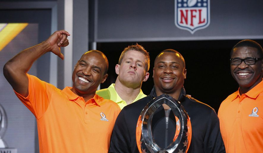 As Troy Vincent, second from right, NFL Executive Vice President of Football Operations, holds the Pro Bowl Trophy, and Michael Irvin, right, NFL Hall of Fame player and Pro Bowl Alumni team captain, the group poses for photographers, Darren Woodson, left, NFL Hall of Fame player and Pro Bowl Alumni co-captain, smiles as he points to Houston Texans Pro Bowl Player J.J. Watt, second from left, who jokingly jumps into the group picture during the Pro Bowl Kickoff news conference Tuesday, Jan. 20, 2015, in Phoenix. (AP Photo/Ross D. Franklin)
