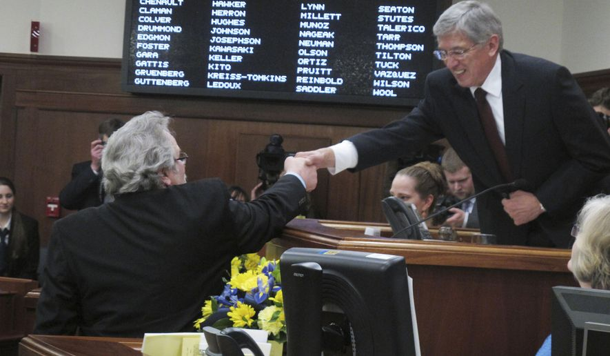 Lt. Gov. Byron Mallott, right, shakes hands with Rep. David Guttenberg, D-Fairbanks, after Guttenberg was sworn in on Tuesday, Jan. 20, 2015, in Juneau, Alaska. Mallott administered the oath of office to lawmakers who won election last year. (AP Photo/Becky Bohrer)
