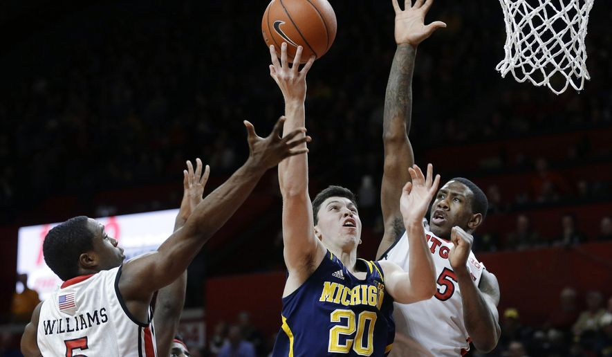 Michigan forward Sean Lonergan (20) takes a shot as he splits Rutgers defenders guard Mike Williams (5) and forward Greg Lewis (35) during the first half of an NCAA college basketball game Tuesday, Jan. 20, 2015, in Piscataway, N.J. (AP Photo/Mel Evans)