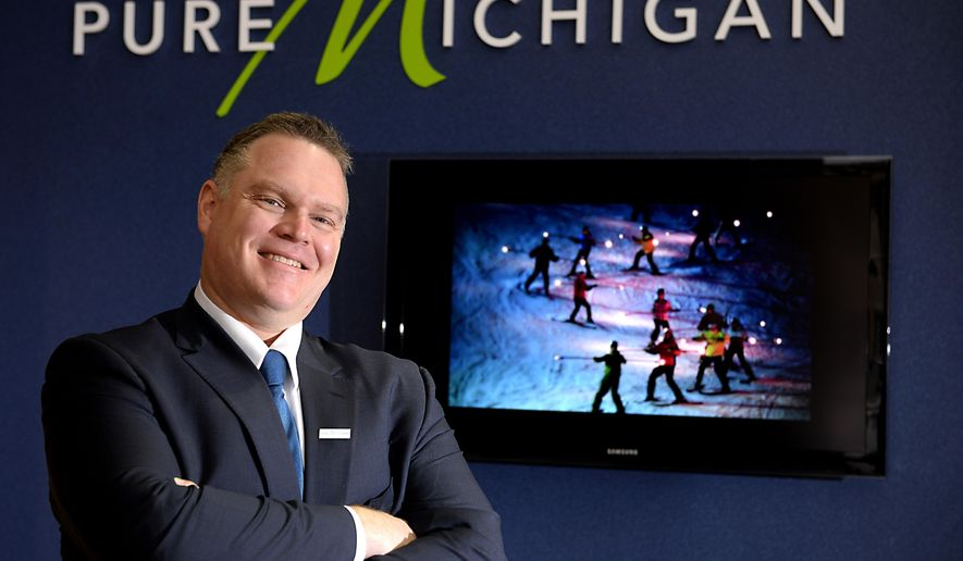 David West, Vice President of Travel Michigan, poses at the Michigan Economic Development Corporation offices  in Lansing, Mich., Jan. 9. 2015. West will lead efforts to boost Michigan destinations and oversee the popular Pure Michigan campaign. Tourism was almost a $19 billion industry in Michigan in 2013, the most recent year for which figures are available. (AP Photo/Lansing State Journal, Rod Sanford)