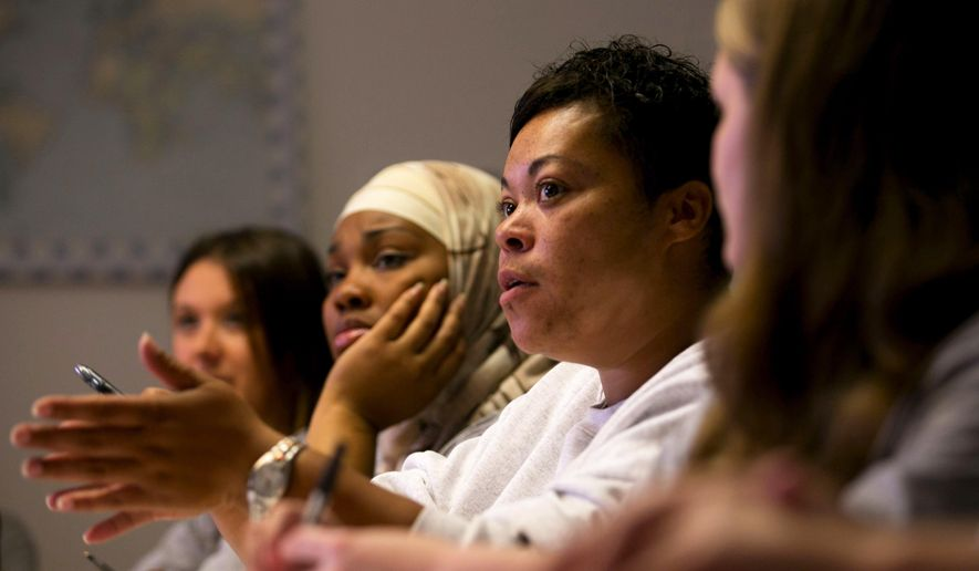In an Oct. 1, 2014 photo, Lisa Kanamu, second from right, joins a discussion during a government class at the Washington Corrections Center for Women near Gig Harbor, Wash. In the past two years, 250 women have taken courses through the Freedom Education Project of Puget Sound. (AP Photo/The Seattle Times, Erika Schultz)  SEATTLE OUT; USA TODAY OUT; MAGS OUT; TELEVISION OUT; NO SALES; MANDATORY CREDIT TO BOTH THE SEATTLE TIMES AND THE PHOTOGRAPHER