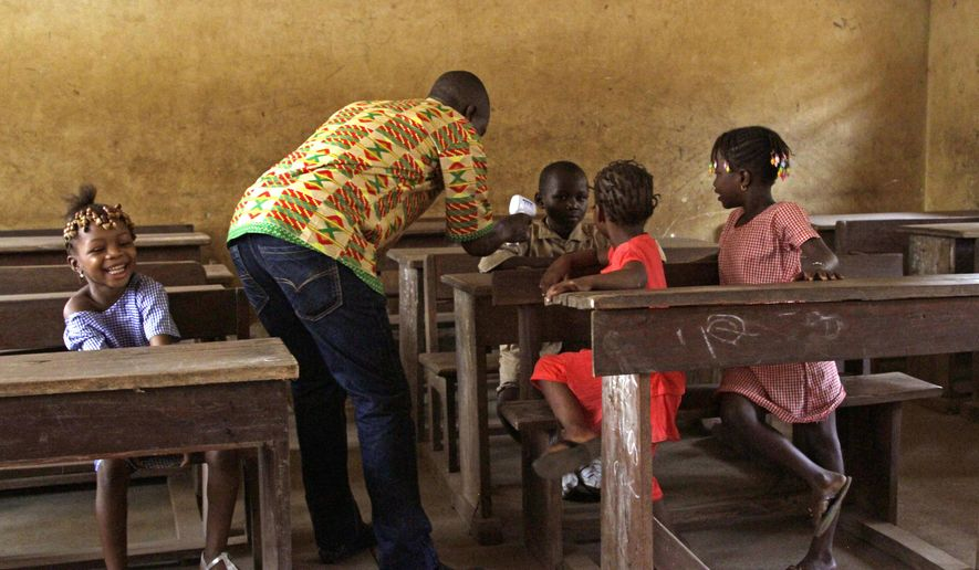 A health care worker, center, takes the temperatures of school children for signs of the Ebola virus inside their classroom, as a child, left, laughs in the city of Conakry, Guinea, Monday, Jan. 19, 2015. Schools shuttered during the height of the Ebola crisis in Guinea began reopening Monday, but many parents were still too afraid to send their children to classes. Employees at the doors of schools in the capital were taking temperatures of everyone who showed up on Monday. (AP Photo/Youssouf Bah)