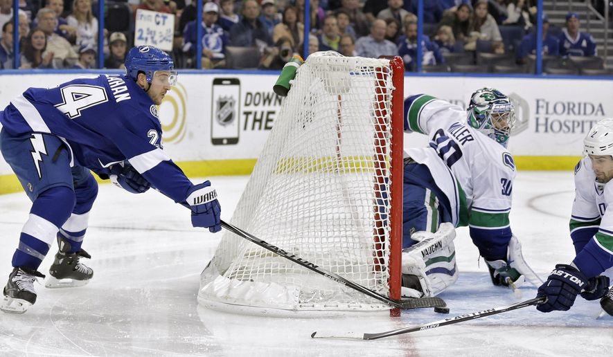 Tampa Bay Lightning right wing Ryan Callahan (24) tries to wrap the puck past Vancouver Canucks goalie Ryan Miller (30) and defenseman Dan Hamhuis (2) during the second period of an NHL hockey game Tuesday, Jan. 20, 2015, in Tampa, Fla. (AP Photo/Chris O'Meara)