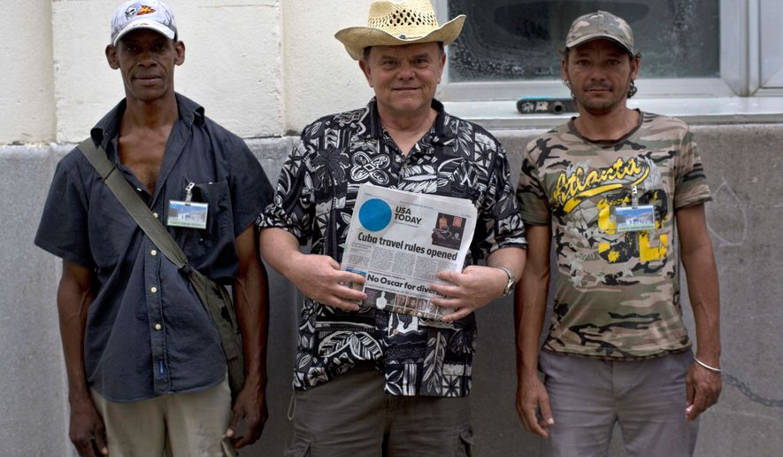 John Koehler, center, a tourist from Wisconsin taking a cultural trip to Cuba, poses for a portrait with locals while holding a copy of USA Today newspaper and showing its front page article on the softening of travel rules for Americans in Havana, Cuba, Tuesday, Jan. 20, 2015. Cuba has so far offered a guardedly positive reception to President Barack Obama's loosening of the trade embargo on Cuba, saying it welcomes the full package of new economic ties on offer, but it insists it will maintain its one-party political system and centrally planned economy. (AP Photo/Ramon Espinosa)