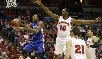 American guard Darius Gardner (0) goes to the basket against Wisconsin forward Nigel Hayes (10) during the first half of a second-round game in the NCAA college basketball tournament Thursday, March 20, 2014, in Milwaukee. (AP Photo/Jeffrey Phelps)