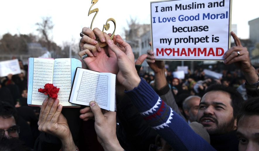 Iranian demonstrators hold copies of the Koran and a decorative metal calligraphy bearing the name of the Prophet Muhammad during a rally against the satirical magazine Charlie Hebdo's latest publication of a cartoon depicting the Prophet Muhammad, which some Muslims deem an insult to Islam, in front of the French Embassy, Tehran, Iran, Monday, Jan. 19, 2015. (AP Photo/Ebrahim Noroozi)