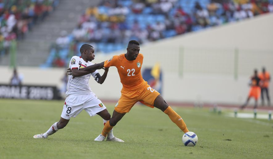 Ivory Coast's Serge Wilfried, right, is tackled by Guinea's Ibrahima Traore' during their African Cup of Nations Group D soccer match in Estadio De Malabo, Equatorial Guinea, Tuesday Jan. 20, 2015. (AP Photo/Sunday Alamba)