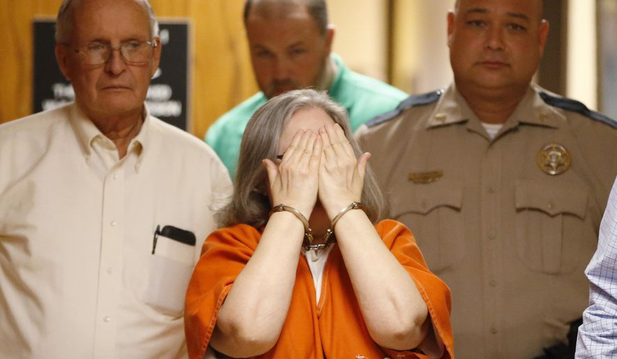 Beverly Noe, 67, covers her face with her hands as she is led from the courtroom after pleading no contest to reduced charges of being an accessory to first-degree murder in the 1992 deaths of two women and a girl whose bodies were found in a septic pit, in Bristow, Okla., Tuesday, Jan. 20, 2015. Noe was sentenced to 15 years in prison after entering the plea to being an accessory to first-degree murder in the deaths that prosecutors said stemmed from a custody dispute over Noe's grandson. (AP Photo/Sue Ogrocki)