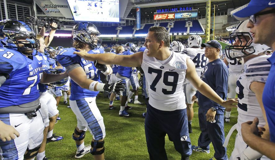 FILE - In this Dec. 22, 2014, file photo, BYU's Latanoa Pikula (79) intercedes in a brawl between opposing players after Memphis defeated BYU Young 55-48 in two overtimes in the inaugural Miami Beach Bowl NCAA college football game in Miami. Memphis announced Tuesday, Jan. 20, 2015, that it will punish 12 Tigers for their role in the brawl. (AP Photo/Wilfredo Lee, File)