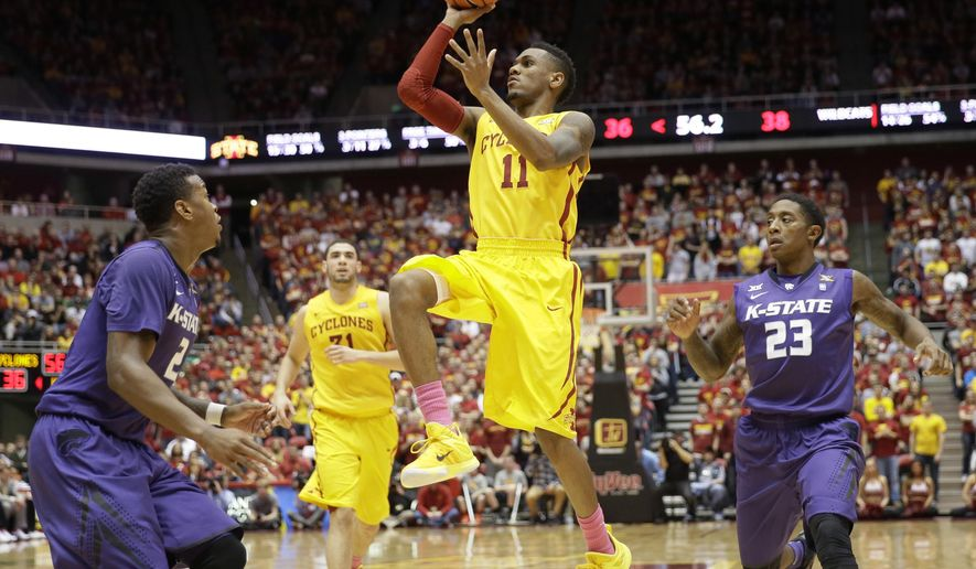 Iowa State guard Monte Morris (11) drives to the basket between Kansas State defenders Marcus Foster, left, and Nigel Johnson (23) during the first half of an NCAA college basketball game, Tuesday, Jan. 20, 2015, in Ames, Iowa. (AP Photo/Charlie Neibergall)