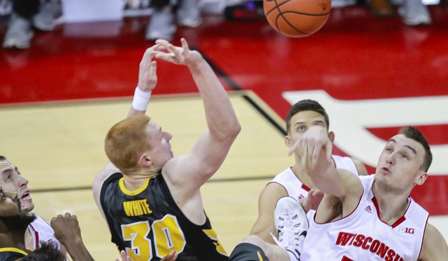 Wisconsin's Sam Dekker (15) bats away a shot by Iowa's Aaron White during the first half of an NCAA college basketball game Tuesday, Jan. 20, 2015, in Madison, Wis. (AP Photo/Andy Manis)
