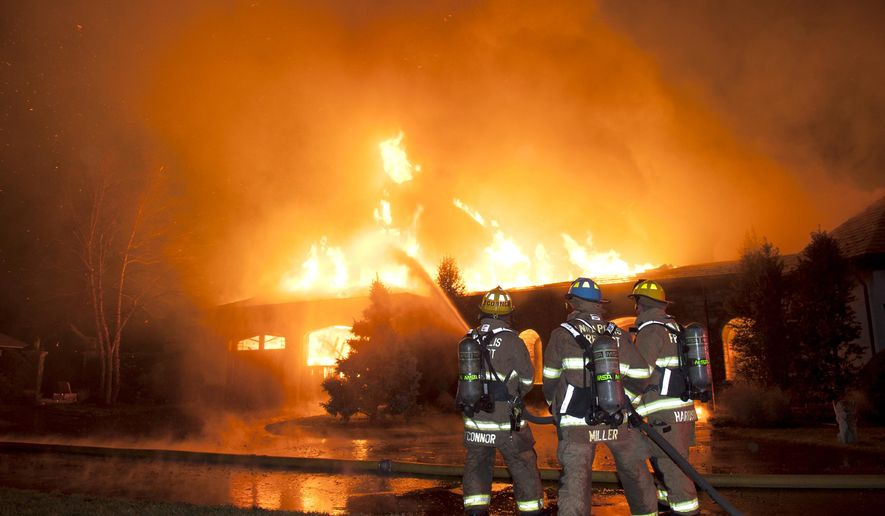 Firefighters battle a four-alarm fire at a home on Childs Point Road, early Monday, Jan. 19, 2015, in Annapolis, Md. The occupants of the home were unaccounted for and fire officials were investigating. (AP Photo/Capital Gazette, Glenn A. Miller)