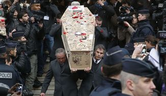 In this file photo dated Thursday, Jan. 15, 2015, pallbearers carry the casket of Charlie Hebdo cartoonist Bernard Verlhac, known as Tignous, decorated by friends and colleagues of the satirical newspaper Charlie Hebdo, at the city hall of Montreuil, east of Paris. (AP Photo/Michel Euler, FILE)