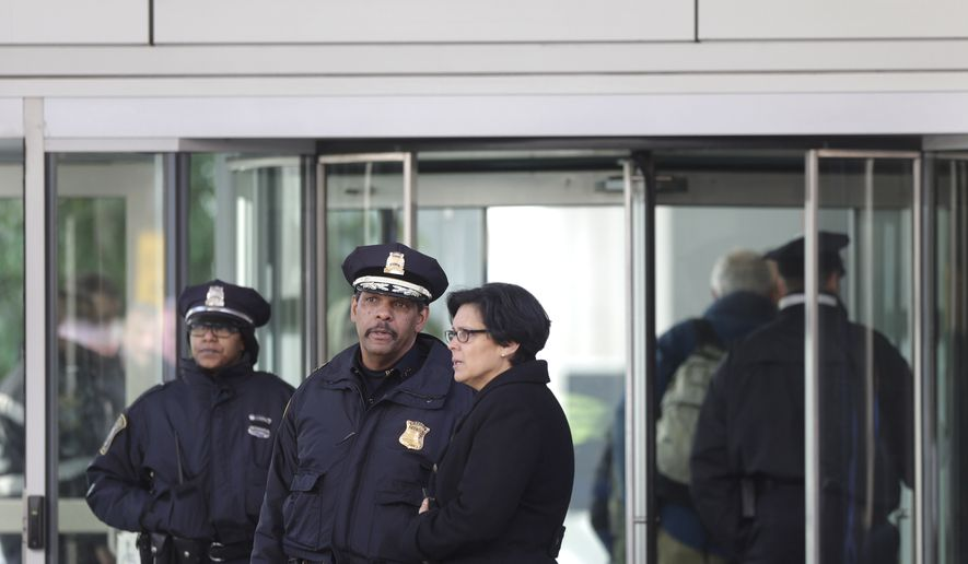 A law enforcement official, center, speaks with an unidentified woman, right, outside the Shapiro building at Brigham and Women's Hospital, Tuesday, Jan. 20, 2015, in Boston. Police say a doctor was shot inside the prestigious Boston hospital before the shooter died of a self-inflicted wound. (AP Photo/Steven Senne)