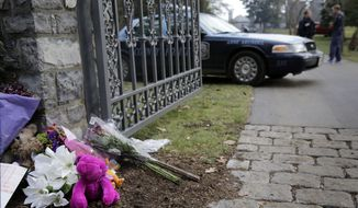 Flowers and teddy bears have been left at the front gate of a waterfront mansion that was gutted Monday by a massive fire, Tuesday, Jan. 20, 2015, in Annapolis, Md. Relatives of six family members who remain unaccounted for after the fire believe they were inside at the time of Monday's blaze, a fire official said Tuesday. (AP Photo/Patrick Semansky)
