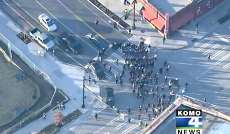 """At least 19 people were arrested and a Seattle police officer suffered a leg injury after """"Black Lives Matter"""" protesters blocked part of State Route 99 Monday afternoon. (KOMO 4 News)"""
