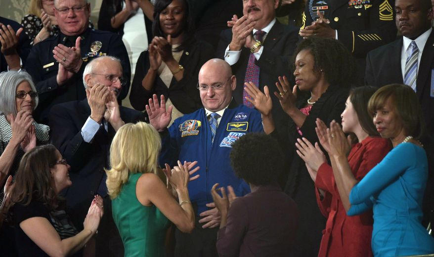 NASA astronaut Scott Kelli acknowledges applause as US President Barack Obama delivers the State of the Union address before a joint session of Congress on January 20, 2015 at the US Capitol in Washington, DC. AFP PHOTO/POOL/MANDEL NGAN
