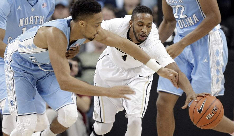 North Carolina's J.P. Tokoto, left, and Wake Forest's Madison Jones, right, chase a loose ball during the first half of an NCAA college basketball game in Winston-Salem, N.C., Wednesday, Jan. 21, 2015. (AP Photo/Chuck Burton)