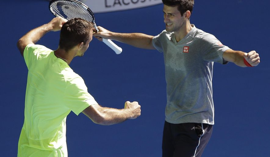 Novak Djokovic of Serbia, right, and his compatriot Viktor Troicki come closer to hug during a training session at the Australian Open tennis championship in Melbourne, Australia, Sunday, Jan. 18, 2015. (AP Photo/Lee Jin-man)