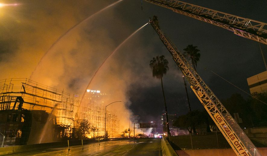 FILE - In this early Monday, Dec. 8, 2014, file photo, Los Angeles County firefighters battle a fire at an apartment building under construction next to the Harbor CA-110 Freeway. A $170,000 reward for information that leads to the person responsible for igniting the huge inferno downtown Los Angeles, was announced at a news conference outside City Hall by city officials on Wednesday, Jan. 21, 2015. (AP Photo/Damian Dovarganes, File)