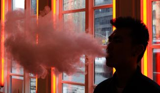 A man exhales vapor from an e-cigarette in New York in this Feb. 20, 2014, file photo. (AP Photo/Frank Franklin II) ** FILE **